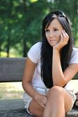 Young pensive woman siting on bench — Stock Photo