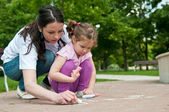 Mother teaches her child drawing on sidewalk — Stock Photo
