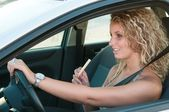 Young woman eating sweets while driving car — Stock Photo