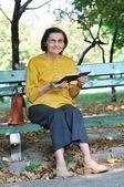Senior woman reading book autdoors — Stock Photo