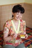 Senior woman eating cake — Stock Photo
