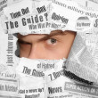 Sceptic look through the newspapers — Stock Photo