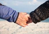 Holding hands on beach — Stock Photo