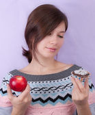 Girl choosing between apple and cupcake — Stock Photo
