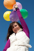 Happy girl holding balloons — Stock Photo
