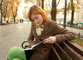 Redhead girl reading in autumn park — Stock Photo