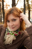 Ragazza sorridente con sciarpa fiorito nel parco d'autunno — Foto Stock