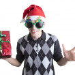 Happy man in Christmas party glasses and hat holds red gift box — Stock Photo #7652106