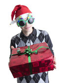 Man in Christmas party glasses and hat holds red gift box — Stock Photo