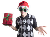 Happy man in Christmas party glasses and hat holds red gift box — Stock Photo