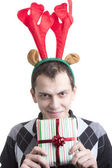 Happy man in Christmas party elk horns holding red gift box — Stock Photo