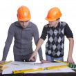 Achitects standing over table with blueprints, rulers and pencil — Stock Photo