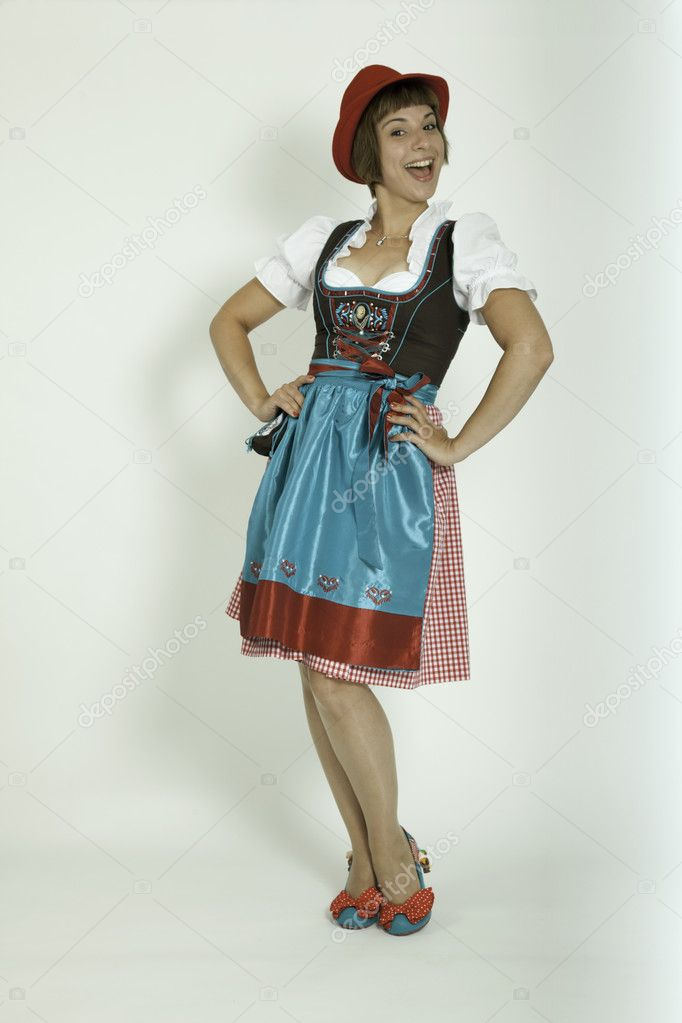 Junge Frau mit Dirndl, verrckten Schuhen und rotem Hut  Stock Photo #7399140