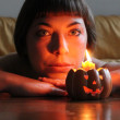 Portrait of girl lighted by a candle pumpkin-shaped — Stock Photo #7280085