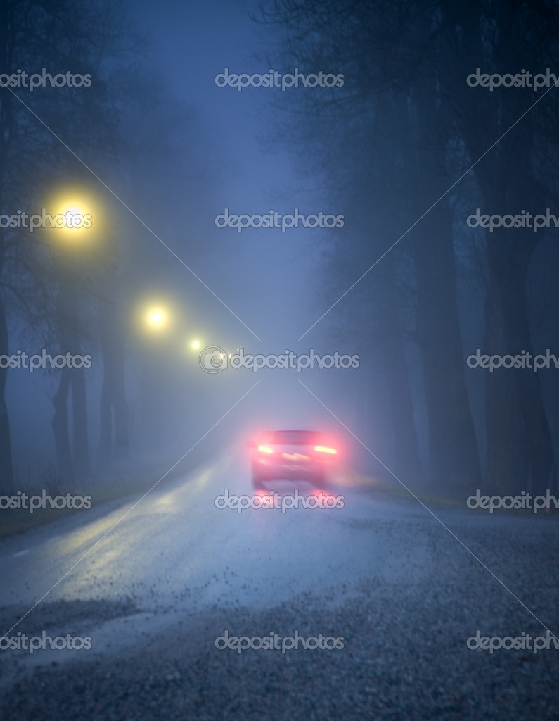 Car driving in a dark avenue in thick fog — Stock Photo #7186234