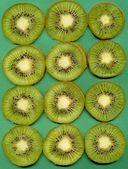 Slices of kiwi fruit on green background — Stock Photo