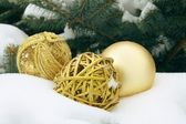Gold ornaments on snow — Stock Photo
