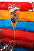 Glass balls in glass and multicolor decorative bottles as background — Stock Photo