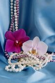 Pearl necklaces and orchids on blue satin — Stock Photo