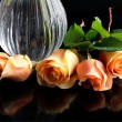 Pink roses and wase on black table — Stock Photo