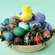 Easter decoration with yellow small chicken and painted eggs in basket — Photo #7867516
