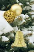 Gold Christmas ornaments on snowy coniferous tree — Stock Photo