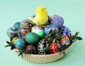 Easter decoration with yellow small chicken and painted eggs in basket — Stock Photo