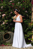 Bride with bouquet in a garden — Stock Photo