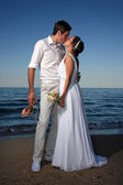 Bride and groom at the beach — Stock fotografie