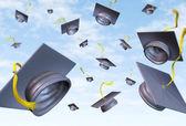 Graduation caps thrown in the air — Stock Photo
