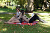 Two young girls sitting in the autumn park — Stok fotoğraf