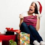 Smiling amazed christmas girl unpacking gifts. Isolated on white — Stock Photo #7539196