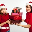 Two smiling christmas girls holding gifts wearing Santa hat. — Stock Photo #7539277