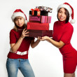 Two smiling christmas girls holding gifts wearing Santa hat. — Stock Photo #7539283