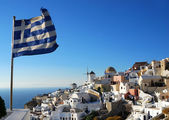 Oia scenery with Greece flag — Stock Photo