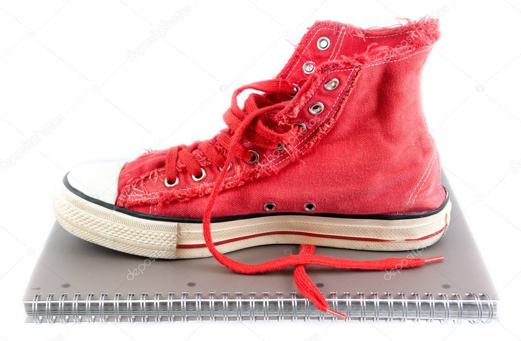Red shoes on a school notebook. On a white background. — Stock Photo #7160918
