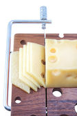 Wooden cutting board with cheese slices — ストック写真