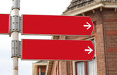 Blank signpost in red with white arrows — Stock Photo