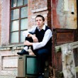 Young man is sitting near old house — Stock Photo