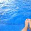 Feet beside the pool — Stock Photo