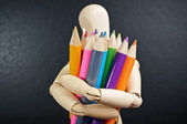 Wooden mannequin holds in hand a set of color pencils — Stock Photo