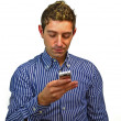 Attractive young man texting on cell phone — Stock Photo