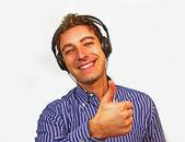 Bravo ragazzo cercando con cuffie, sorridente, pollice alzato — Foto Stock