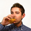 Attractive young man drinking fruit juice — Stock Photo #7943510