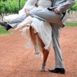 Bride and groom lifting legs on dust road — Stock Photo