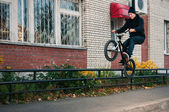 Biker doing icepick grind trick — Stock Photo