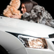 Girl laying on car hood with plush toy — Stockfoto