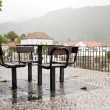 Stock Photo: Seats and table under rain, with view to village
