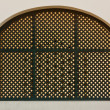 Old arch metal grid window on white wall — Stock Photo
