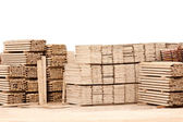 Pile of wooden planks in gravel ground against white wall — Stock Photo